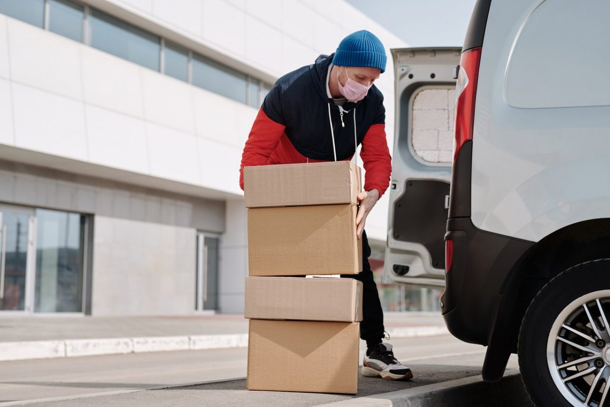 A man delivers packages to a business.