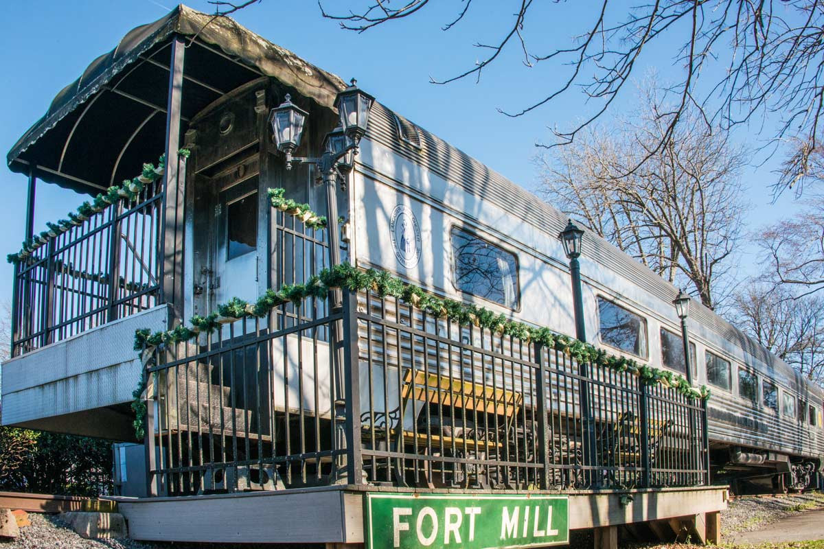 older train decorated with christmas decor with green fort mill sign