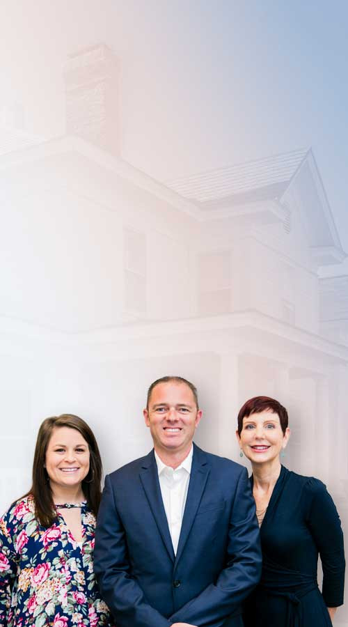 the team at independence insurance associates smiling with a faded white house in the background
