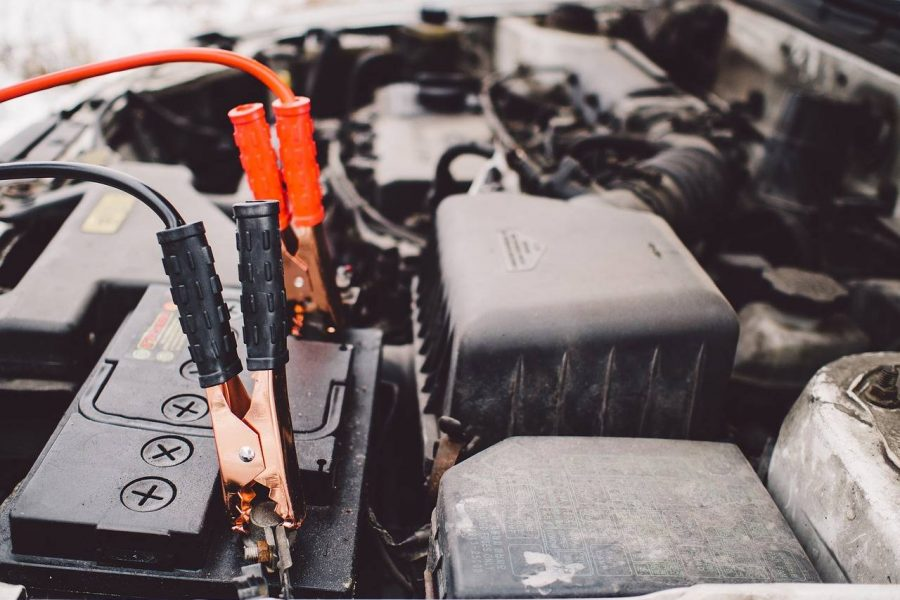 red and black cables charging a car battery