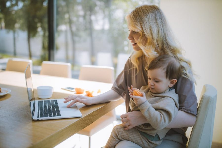 A woman scrolls her computer with her child.