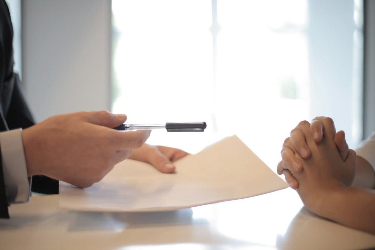 Two people prepare to sign a contact.