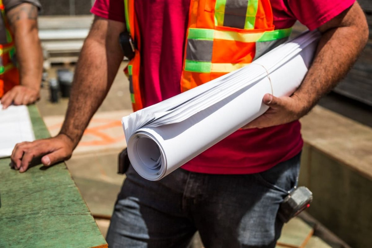 A construction worker holds the blueprint.