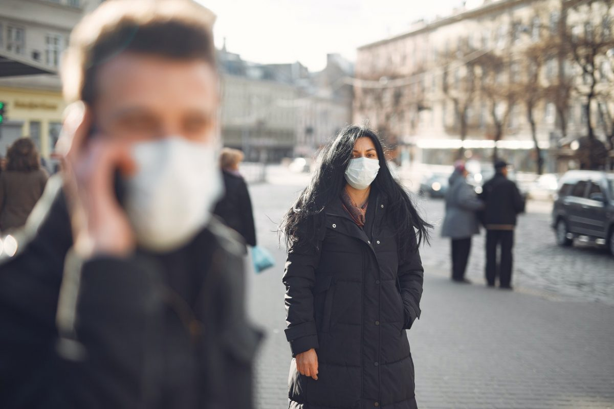 Two individuals wear their masks.