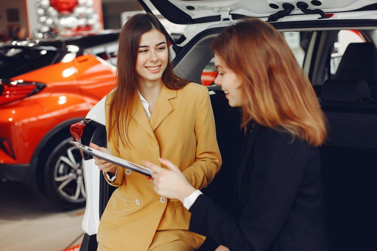 A woman buys a new car.