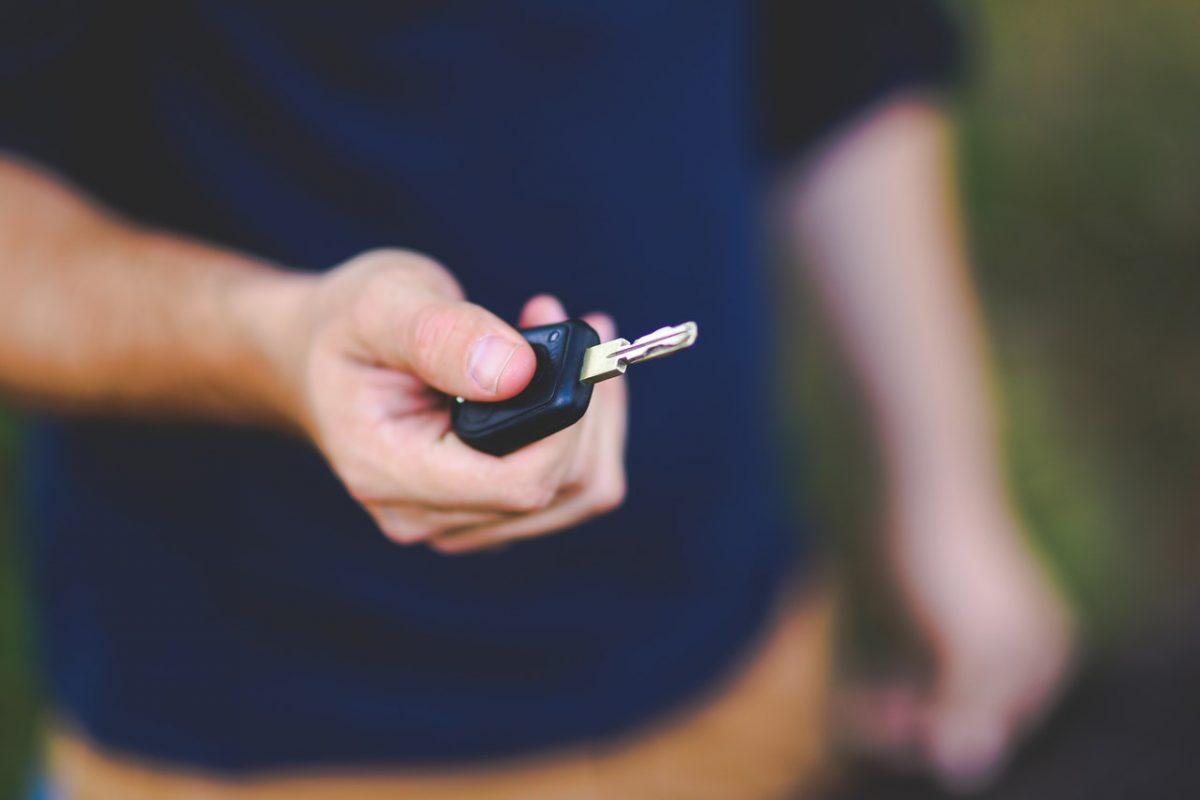 A man holds a pair of car keys.