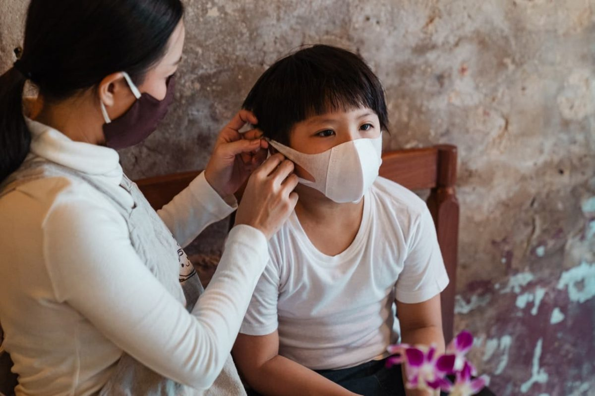 A mother fixes her child's mask.