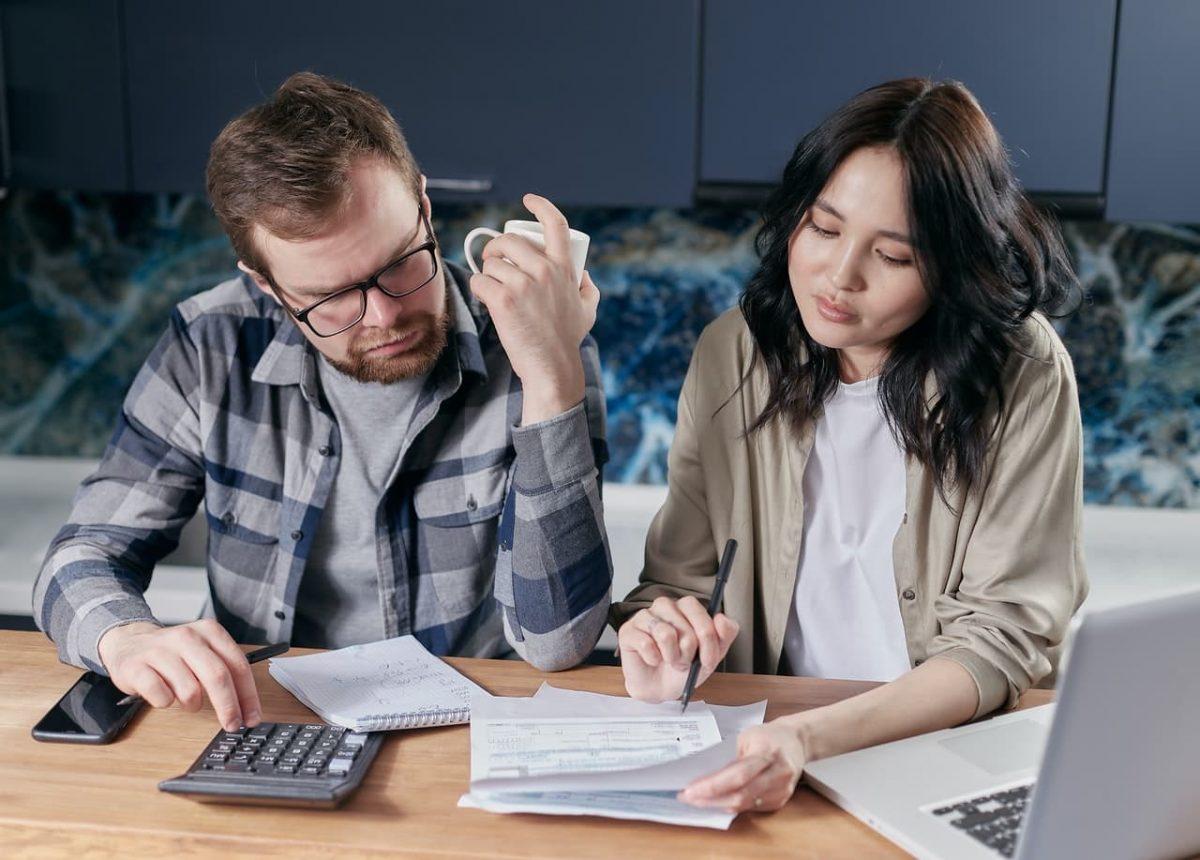 A couple analyzes their bills.