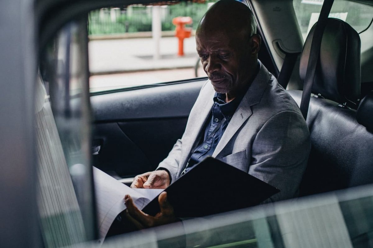 A man looks over documents in his car.