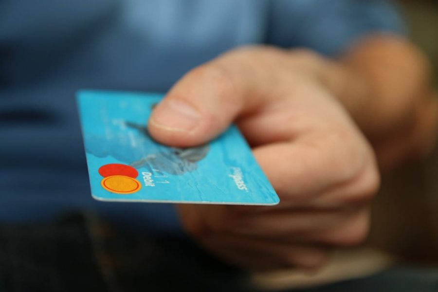 A person hands over their credit card.