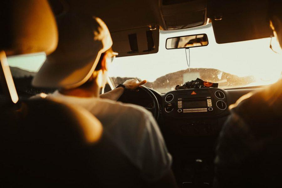 A man drive his car toward the sunset.